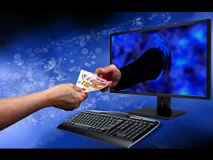 A hand taking money through a monitor - online shop